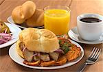 Typical Peruvian breakfast consisting of Pan con Chicharron (Bun with fried meat) and fried sweet potato, tamal (on the left), salsa criolla (onion salad) with coffee, orange juice and buns (Selective Focus, Focus on the front) Stock Photo - Royalty-Free, Artist: ildi                          , Code: 400-04859668
