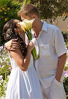 A young newly married couple sharing a romantic kiss Stock Photo - Royalty-Freenull, Code: 400-04860159