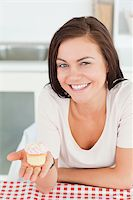 Laughing brunette showing a cupcake in her kitchen Stock Photo - Royalty-Freenull, Code: 400-04884072
