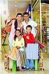 Portrait of a happy family of four in store looking at camera and smiling Stock Photo - Royalty-Free, Artist: pressmaster                   , Code: 400-04892065