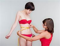two young female friends measuring results of diet - isolated on gray Stock Photo - Royalty-Freenull, Code: 400-04896754
