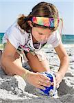 Happy girl building sandcastle on a beach