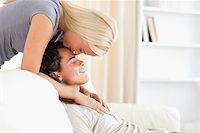 Woman kissing her fiance on the forehead in their living room Stock Photo - Royalty-Freenull, Code: 400-04905752