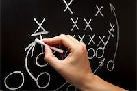 strategy - Man drawing a game strategy with white chalk on a blackboard. Stock Photo - Royalty-Freenull, Code: 400-04906145