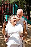 Senior couple on a playground, swinging on the swingset. Stock Photo - Royalty-Free, Artist: lisafx                        , Code: 400-04907430