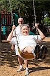Senior woman swinging on the playground in the park.  Her husband is pushing her. Stock Photo - Royalty-Free, Artist: lisafx                        , Code: 400-04907431