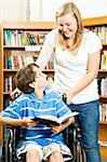 Teen girl and disabled boy in the school library. Stock Photo - Royalty-Free, Artist: lisafx                        , Code: 400-04907438
