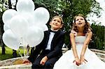 Portrait of children bride and groom with balloons sitting in park Stock Photo - Royalty-Free, Artist: pressmaster                   , Code: 400-04919868