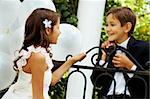 Portrait of boy groom and his cute bride chatting in park Stock Photo - Royalty-Free, Artist: pressmaster                   , Code: 400-04919917