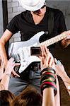 Rock guitarist playing in front of a cheering crowd.