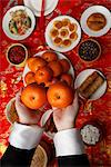 Hands holding oranges over table with Chinese food Stock Photo - Premium Royalty-Free, Artist: AWL Images, Code: 656-04926605