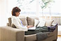 Woman sitting on sofa and surfing internet Stock Photo - Premium Royalty-Freenull, Code: 6102-04929454