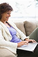 Woman sitting on sofa and surfing internet Stock Photo - Premium Royalty-Freenull, Code: 6102-04929455