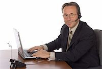 isolated businessman at the desk with headset Stock Photo - Royalty-Freenull, Code: 400-04941174