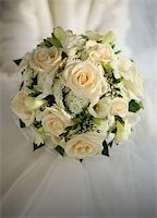 Wedding bouquet from beige roses on a background of a wedding dress Stock Photo - Royalty-Freenull, Code: 400-04941374