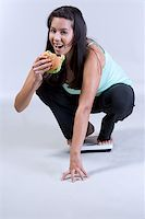 Female on weight scale eating hamburger Stock Photo - Royalty-Freenull, Code: 400-04944602