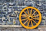 An old yellow wooden wagon wheel leaning against a stone wall Stock Photo - Royalty-Free, Artist: sbonk                         , Code: 400-04954009