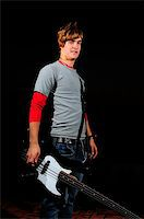 Portrait of young trendy electric bass player isolated Stock Photo - Royalty-Freenull, Code: 400-04999286