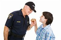 Adolescent boy giving a donut to a friendly police officer.  Isolated on white. Stock Photo - Royalty-Freenull, Code: 400-05007243