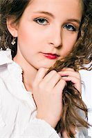 Studio portrait of a young girl made up as a glamourish woman Stock Photo - Royalty-Freenull, Code: 400-05022069