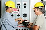 Electricians measuring the voltage output on an industrial power distribution center.  All work is being performed according to industry code and safety standards. Stock Photo - Royalty-Free, Artist: lisafx                        , Code: 400-05022334