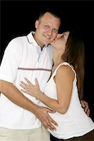 Beautiful pregnant woman giving her husband a kiss.  Black background. Stock Photo - Royalty-Freenull, Code: 400-05023126