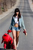 running away scared - Young woman in the middle of the road with her teddy bear. Stock Photo - Royalty-Freenull, Code: 400-05040026