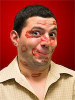 man portrait with many kisses on his face Stock Photo - Royalty-Freenull, Code: 400-05057334