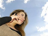 young woman speaks by mobile phone on  background of  sky Stock Photo - Ro