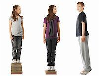 Two smaller girls standing on a pile of books and a boy standing on tiptoe Stock Photo - Royalty-Freenull, Code: 400-05068306