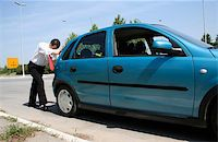 Man pushing a broken car or a car out of gas Stock Photo - Royalty-Freenull, Code: 400-05068335