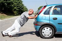 Man pushing a broken car or a car out of gas Stock Photo - Royalty-Freenull, Code: 400-05068357