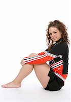 Pretty cheerleader sitting against a white background. Stock Photo - Royalty-Freenull, Code: 400-05074883