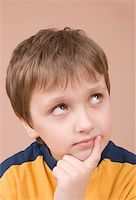 Young boy thinking hard isolated on beige Stock Photo - Royalty-Freenull, Code: 400-05088379