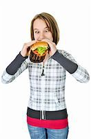 Teenage girl eating a big hamburger isolated on white background Stock Photo - Royalty-Freenull, Code: 400-05094732