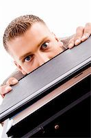 close up of professional man peeping from files on an isolated background Stock Photo - Royalty-Freenull, Code: 400-05102612
