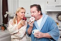 Couple in Kitchen Eating Donut and Coffee or Healthy Fruit. Stock Photo - Royalty-Freenull, Code: 400-05106586