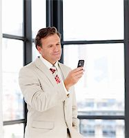Portrait of a mature businessman sending a message on his cell-phone Stock Photo - Royalty-Freenull, Code: 400-05145011