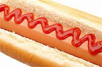 A hot dog with ketchup isolated on white background. Shallow depth of field Stock Photo - Royalty-Freenull, Code: 400-05149273