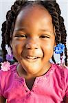 An adorable little african american girl in a pink shirt