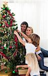 Smiling family hanging decorations on a Christmas tree at home Stock Photo - Royalty-Free, Artist: 4774344sean                   , Code: 400-05185873