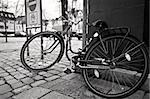Old bicycle on street corner; in black and white