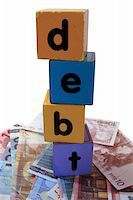 assorted childrens toy letter building blocks against a white background on money that spell debt Stock Photo - Royalty-Freenull, Code: 400-05241315