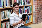 Handsome male student reading a book sitting on the floor in a bookshop Stock Photo - Royalty-Free, Artist: 4774344sean                   , Code: 400-05259230
