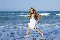 Little girl running beach shore splashing water in blue sea Stock Photo - Royalty-Freenull, Code: 400-05273743