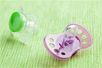 silicone pacifier on green background Stock Photo - Royalty-Freenull, Code: 400-05278335