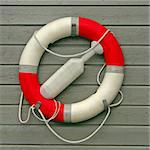 Red-White Lifebuoy with paddle on gray wooden background