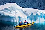 Two men in a canoe among icebergs in Antarctica