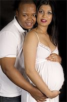 Sexy beautiful pregnant Indian woman and african male embracing in white dress smiling on black backdrop Stock Photo - Royalty-Freenull, Code: 400-05302903