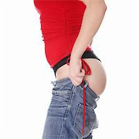 Woman trying to get in to old jeans. Isolated on white Stock Photo - Royalty-Freenull, Code: 400-05318231